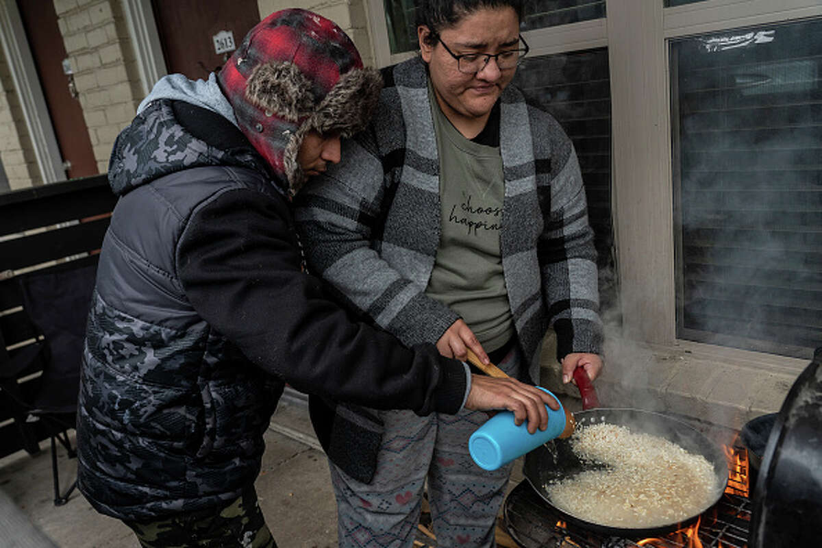 HOUSTON, TX - FEBRUARY 16: Victor Zelaya and Esperanza Gonzalez cook rice on a barbecue grill during power outage caused by the winter storm on February 16, 2021 in Houston, Texas. Winter storm Uri has brought historic cold weather, power outages and traffic accidents to Texas as storms have swept across 26 states with a mix of freezing temperatures and precipitation.