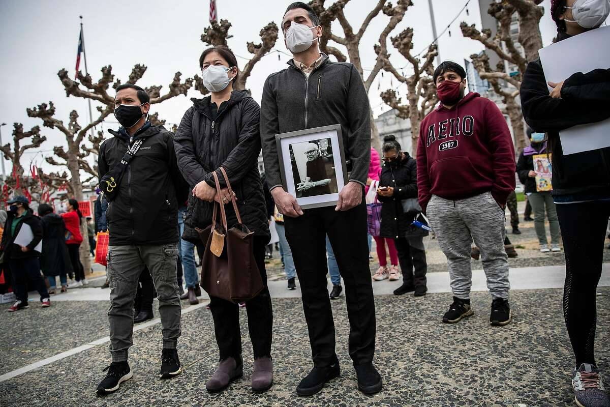"""(L-R) Sanan Wannachit, Monthanus Ratanapakdee, and husband Eric Lawson stand amongst the crowd as Lawson holds a photograph of his late father-in-law Vicha Ratanapakdee while attending """"Love our People: Heal our Communities"""" rally at Civic Center Plaza in condemnation of the recent increase in violence towards the Asian American community around the Bay Area in San Francisco, California Sunday, Feb. 14, 2021. The elder Ratanapakdee, 84, was violently shoved to the ground in broad daylight on Jan. 28 while out on a morning walk in the city's Anza Vista neighborhood and succumbed to his injuries days later."""
