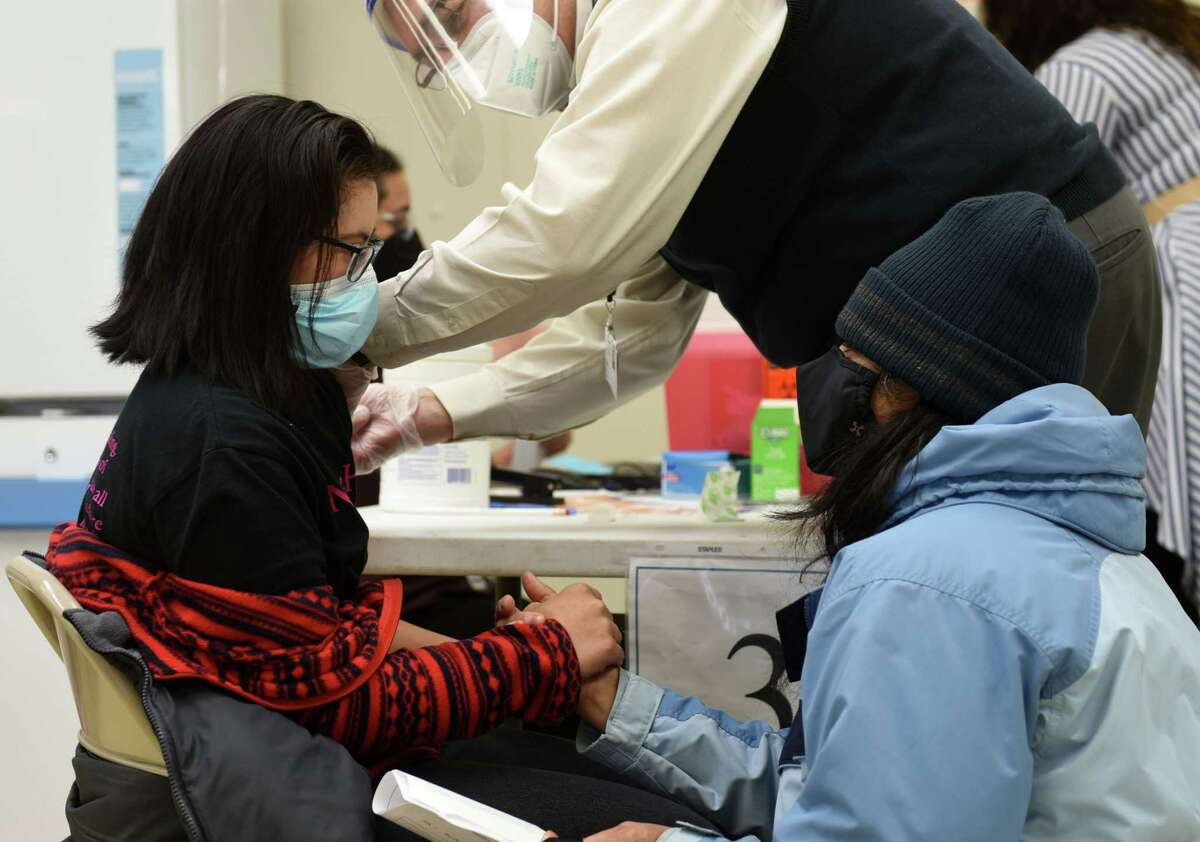 Roshni Modasi, left, is comforted by her mother, Namita, right, who held her hand while she received a COVID-19 vaccine injection during a vaccination clinic on Wednesday, Feb. 17, 2021, at the Center for Disability Services in Albany, N.Y. Albany County and Albany Medical Center, with the approval of the New York State Health Department, allocated 450 dosages of the Moderna COVID-19 vaccine to be administered to people who live in groups homes for persons with intellectual and developmental disabilities, as well as the workers who care for them. (Will Waldron/Times Union)