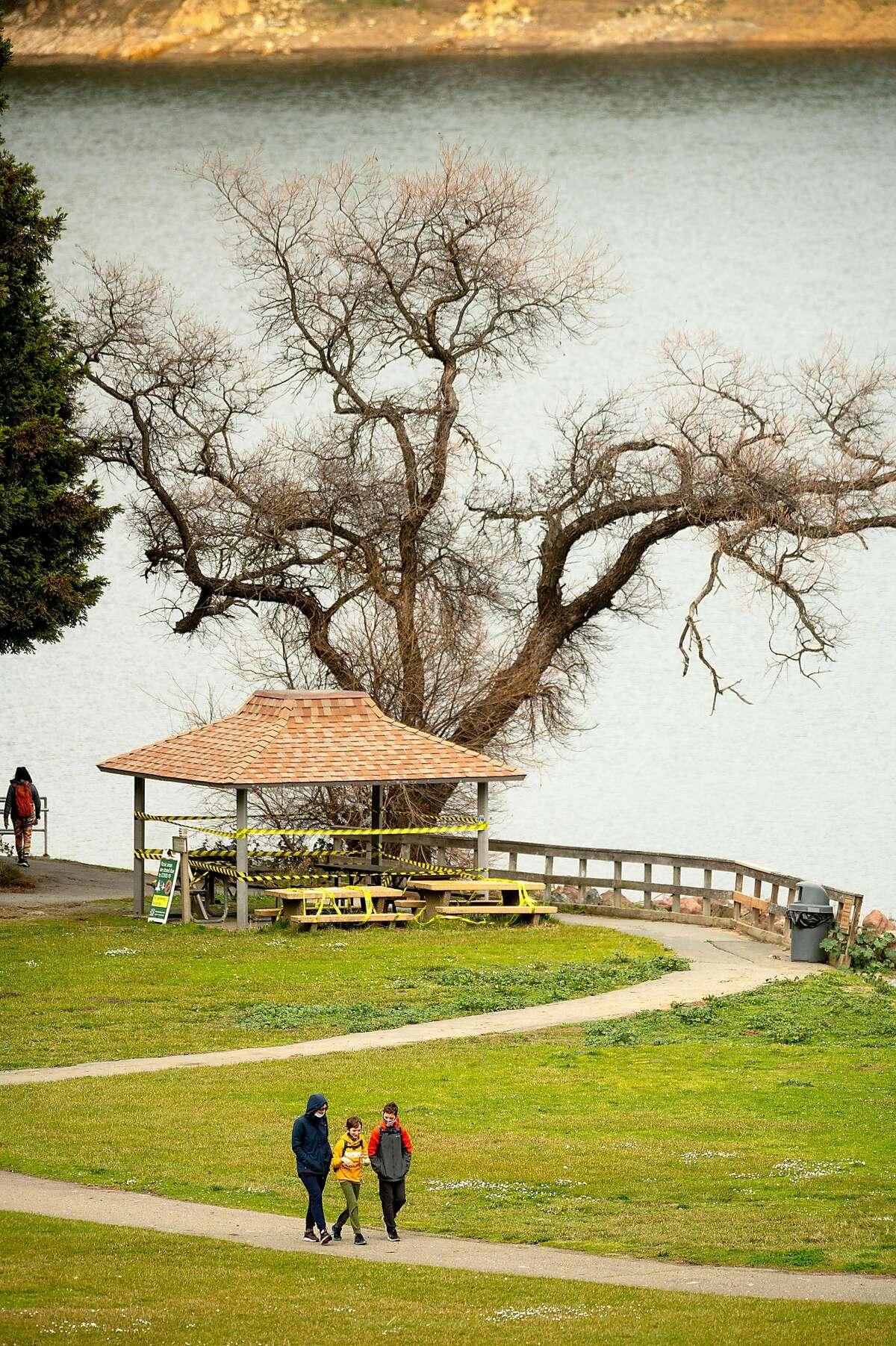 Visitors walk along a path at San Pablo Reservoir on Sunday, Feb. 14, 2021, in El Sobrante, Calif.