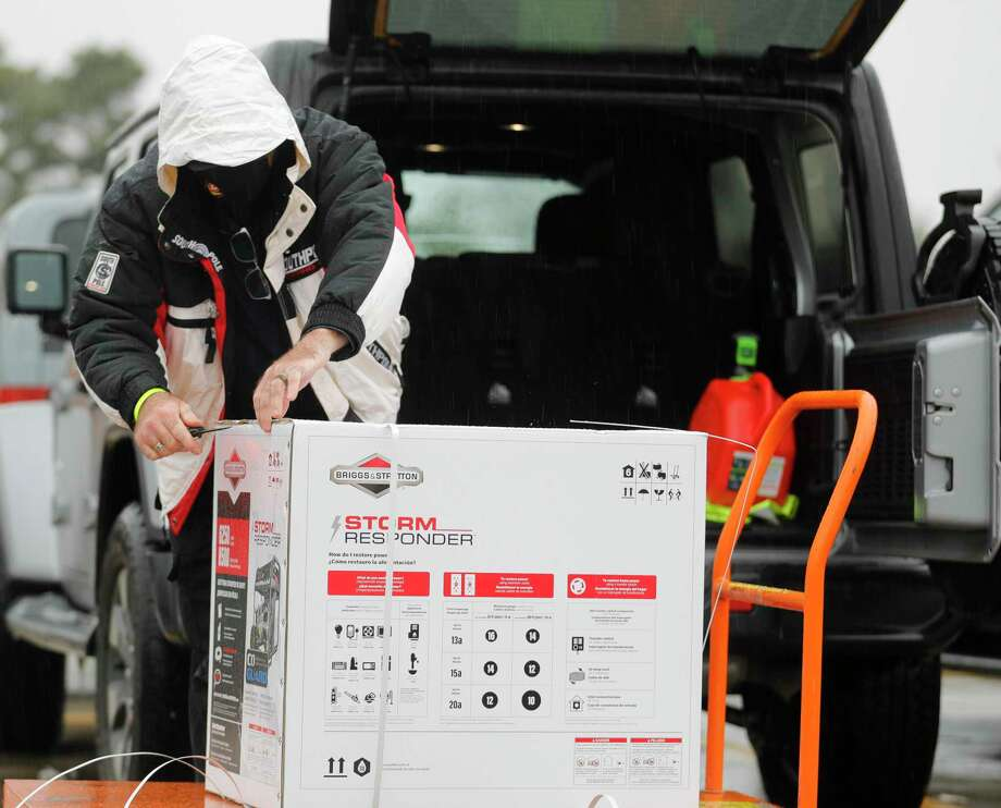 Chris Bodin unpacks a generator in the rain to help warm his family's show chickens, Wednesday in Shenandoah. Bitter cold conditions caused by a historic winter storm continued Wednesday across Montgomery County as lack of water and low water pressure due to busted pipes has now become the bigger concern over loss of power. Photo: Jason Fochtman, Houston Chronicle / Staff Photographer / 2021 © Houston Chronicle