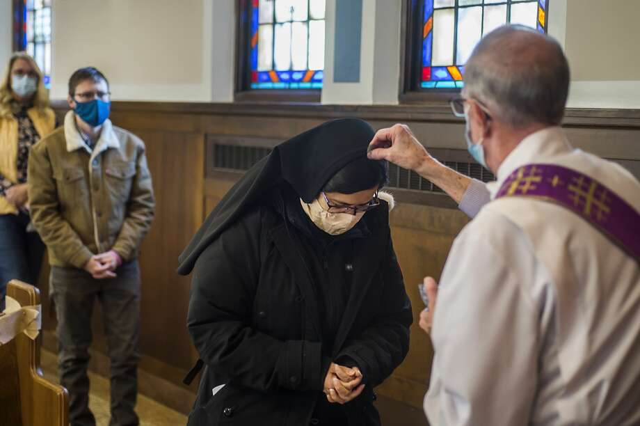 Deacon Al Oliver, right, places ashes onto the head of Sister Maria Jose, center, as congregants of Saint Brigid Catholic Church gather for an Ash Wednesday service Wednesday, Feb. 17, 2021 at the church in Midland. Typically the ashes are placed in the shape of a cross on the forehead, but this year the ashes were sprinkled overhead to mitigate the spread of COVID-19. (Katy Kildee/kkildee@mdn.net) Photo: (Katy Kildee/kkildee@mdn.net)