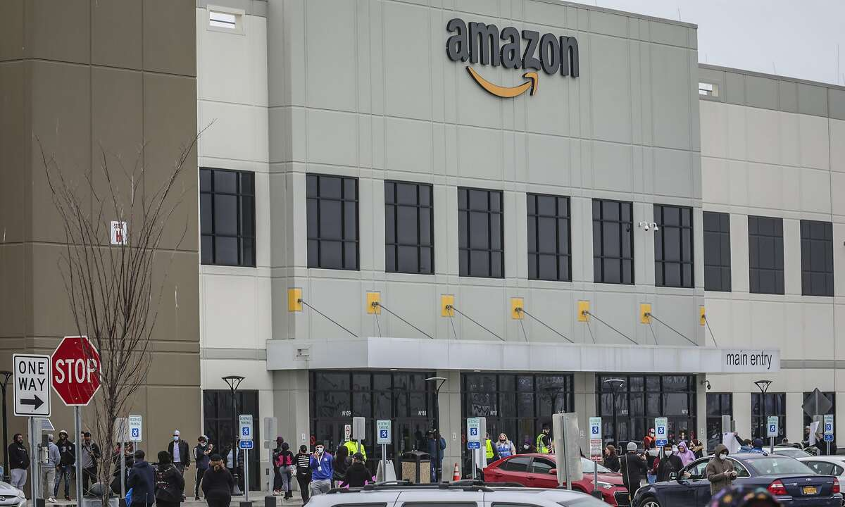 FILE - In this March 30, 2020 file photo, workers at Amazon's fulfillment center in Staten Island, N.Y., gather outside to protest work conditions in the company's warehouse in New York.