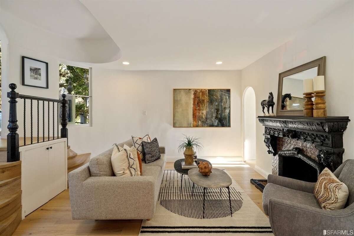 The living room is just off the street-level entry and has two small staircases leading down from the front door, as well as one of home's three decorative fireplaces.