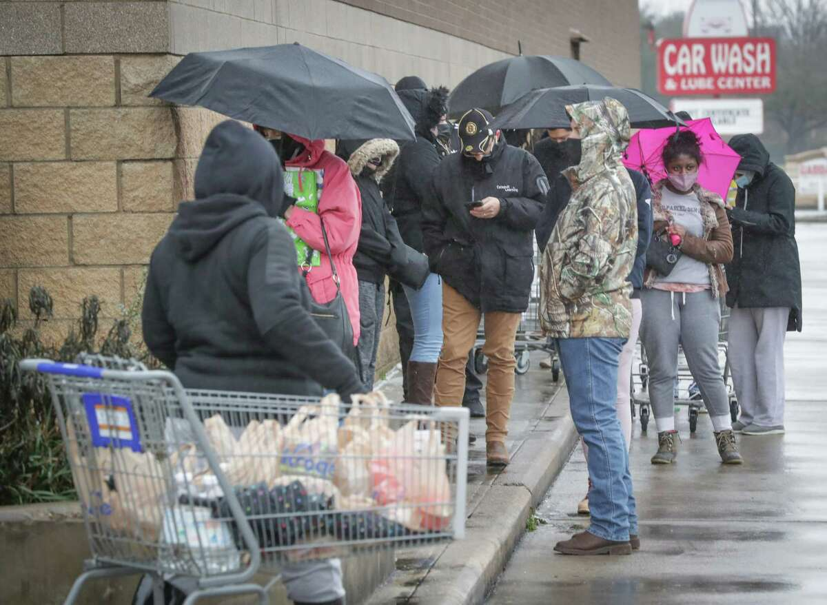 People stand in line outside Kroger, 10306 S Post Oak Rd, waiting to find items to get them through the cold weather Wednesday, Feb. 17, 2021, in Houston.
