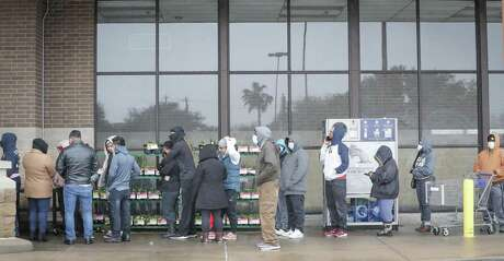 Customers waiting to find items to get them through the power and water outages stand in line Wednesday outside Kroger in Houston's Meyerland neighborhood.
