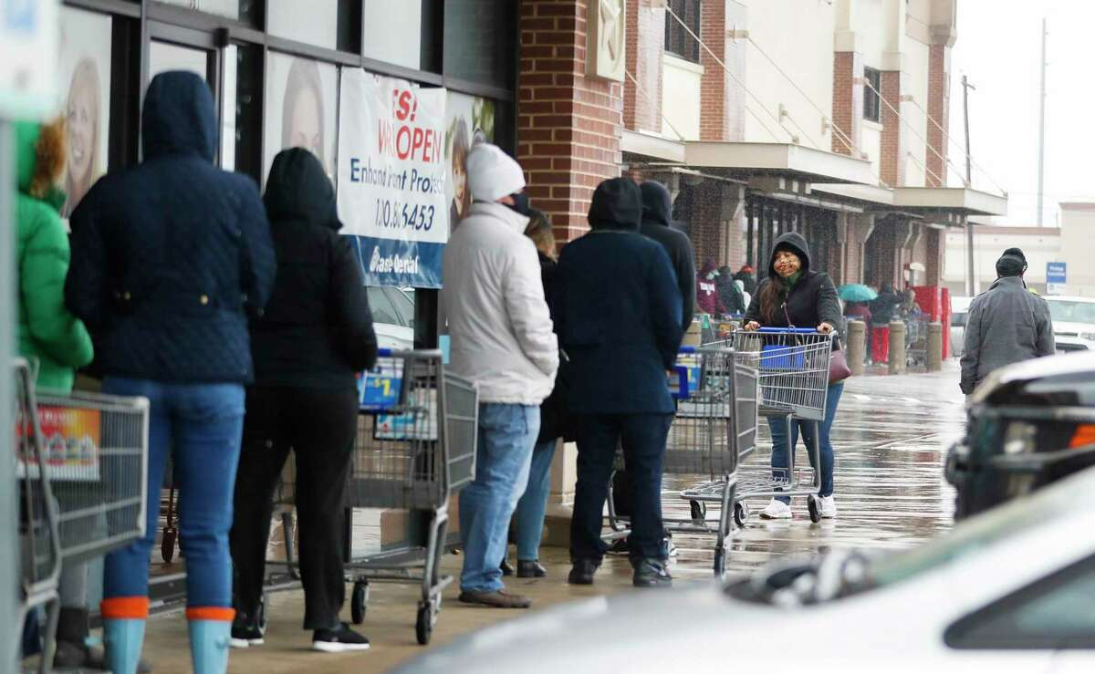 A line of about 100 people wait to get in the Korger grocery store on 11th Street in the Heights, in Houston, Wednesday, February 17, 2021, after a winter storm left people without power and water along with freezing temperatures.