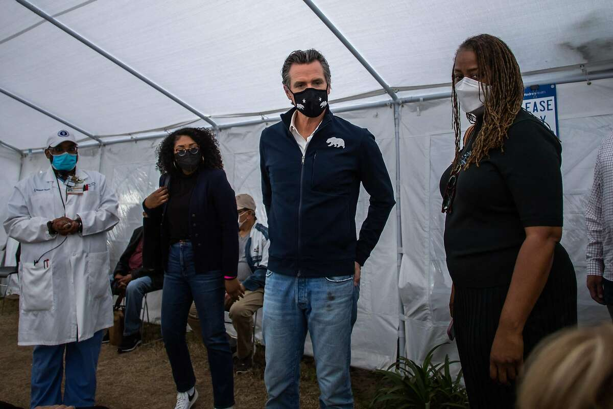 California Governor Gavin Newsom talks to a person that got inoculated with the Moderna Covid-19 vaccine at a vaccination site in Los Angeles on Tuesday. California's positivity rate has plunged since December - a good sign.