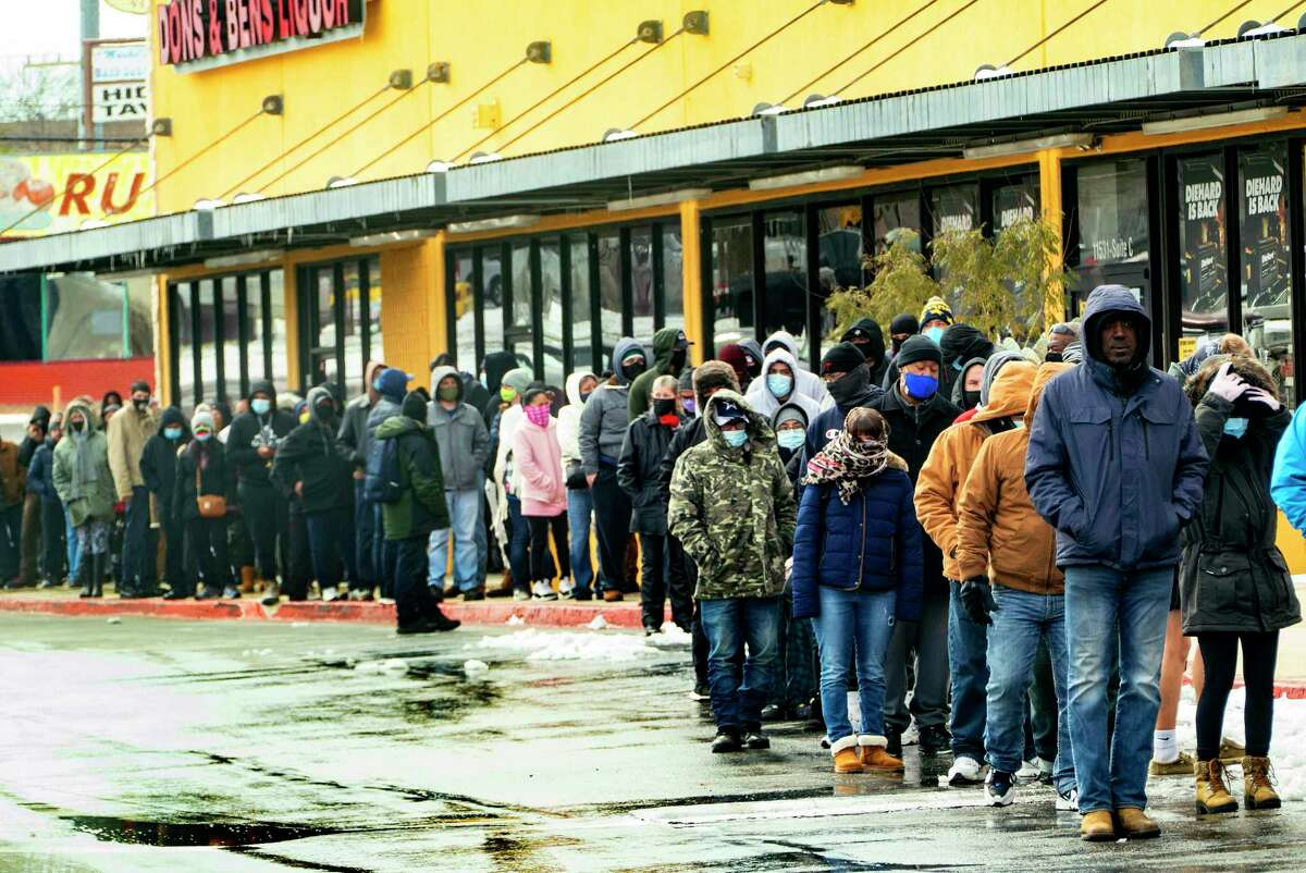 As the snow melts and people venture out, a local doctor reminds San Antonio residents that COVID-19 is still out there, and social distancing measures still apply. Pictured here, hundreds of San Antonians stand in line to enter the H-E-B at West Avenue and Blanco Road on Tuesday.