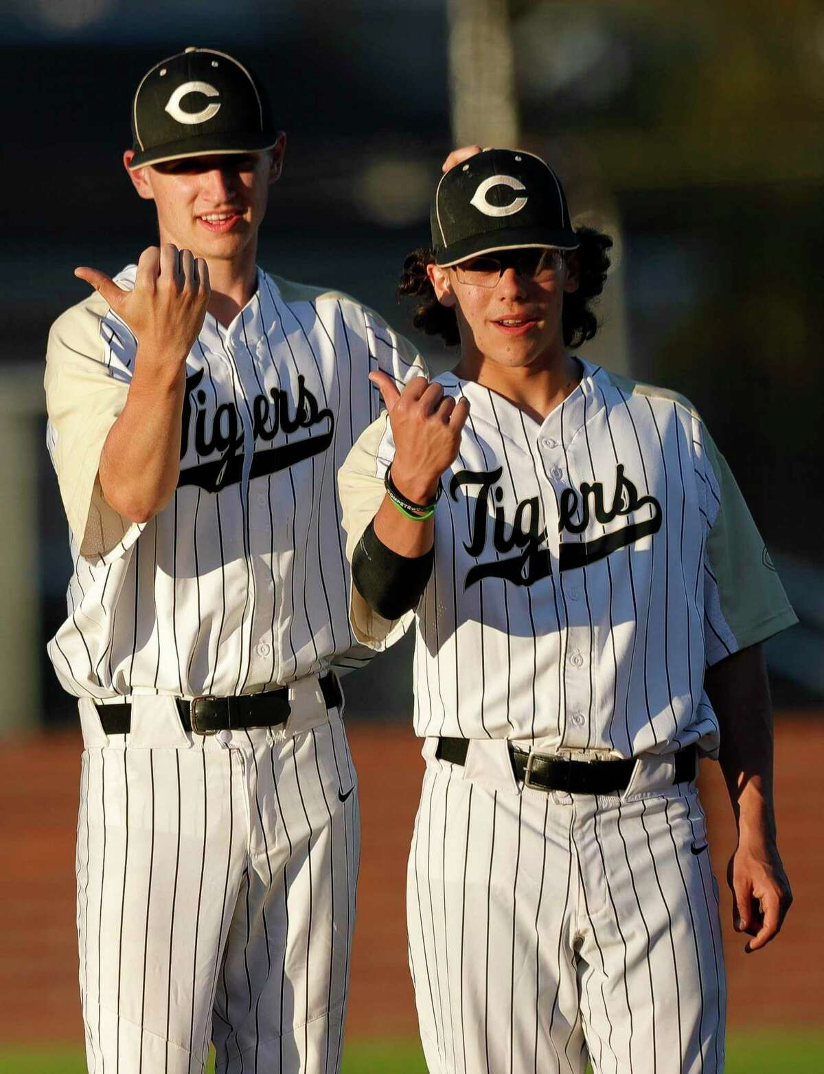 Conroe's Garet Cross, left, alongside Frankie Olivarez helps guide Brendan LaBarrge paints the first base line before a high school baseball game against The Heights during the Ferrell Classic at Conroe High School, Thursday, March 5, 2020, in Conroe.