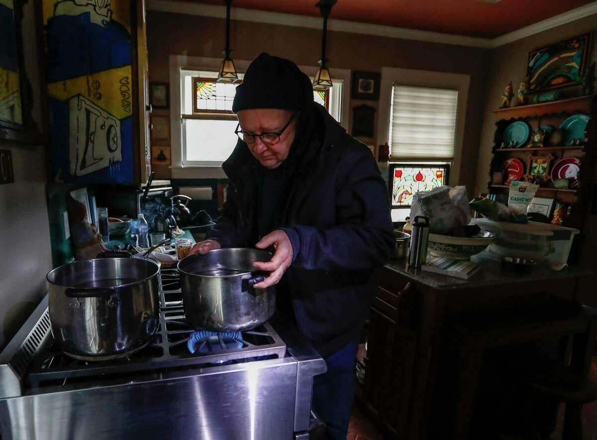 Heights resident Bill Weinle boils water on his stove to add heat in his home, which was without power and water, in Houston, Wednesday, February 17, 2021, after a winter storm left people without power and water along with freezing temperatures.