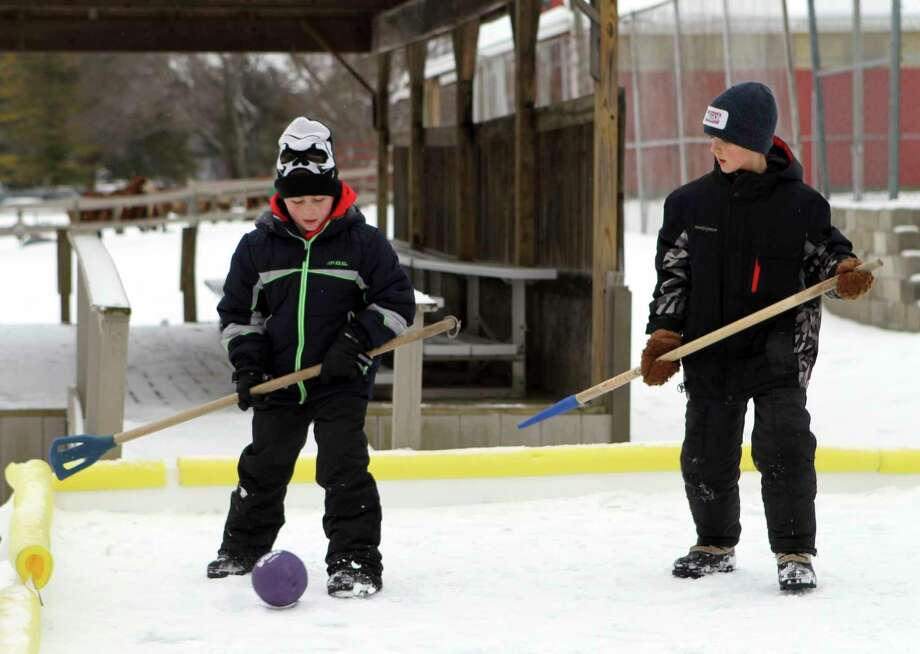 In this Jan. 24, 2021 file photo, acouple of broomball players adjust their footing before resuming playduring an intense game held at Winterfest. CranHill Ranch will host a second installment of Winterfest this Sunday. (Pioneer file photo)