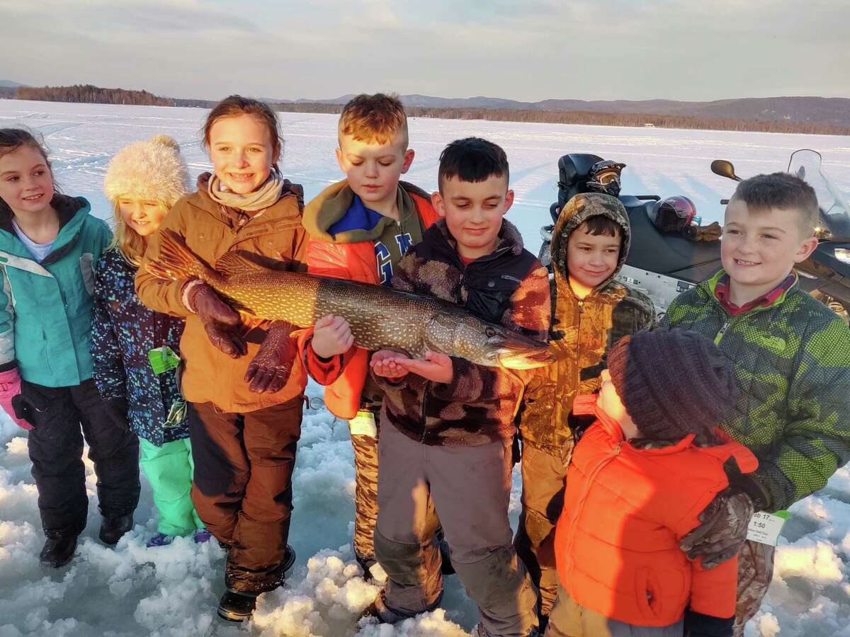 From left, Harper Richardson, Ella Hammons, Macy Weaver, Carter Richardson, Cole Kemper, Callan Kemper, Logan Hammons and Parker Kemper Brown (in orange) with a pike that was released in February of 2020.