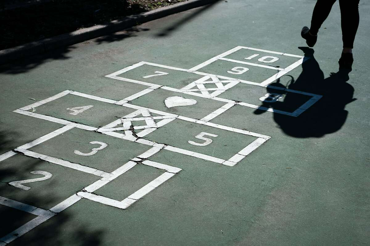 A reporter walks past a hopscotch area outside at Sunset Elementary School in San Francisco, Calif., on Wednesday, Feb. 17, 2021.