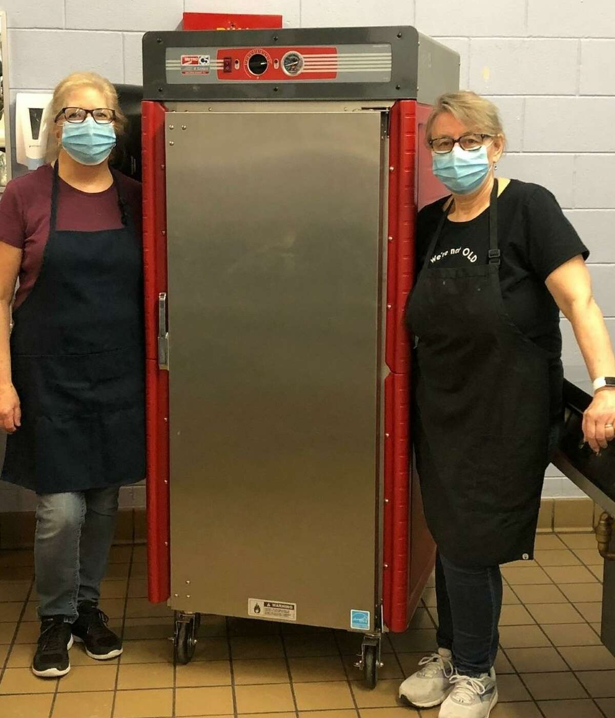 Two nutrition services staff members stand next to a new transport warmer at Kennedy Elementary School.