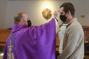The Rev. Christopher Ford distributes ashes to Jimmy Fahey, of Danbury, during Ash Wednesday Mass at St. Gregory the Great Church in Danbury, Conn, on Wednesday, February 17, 2021.