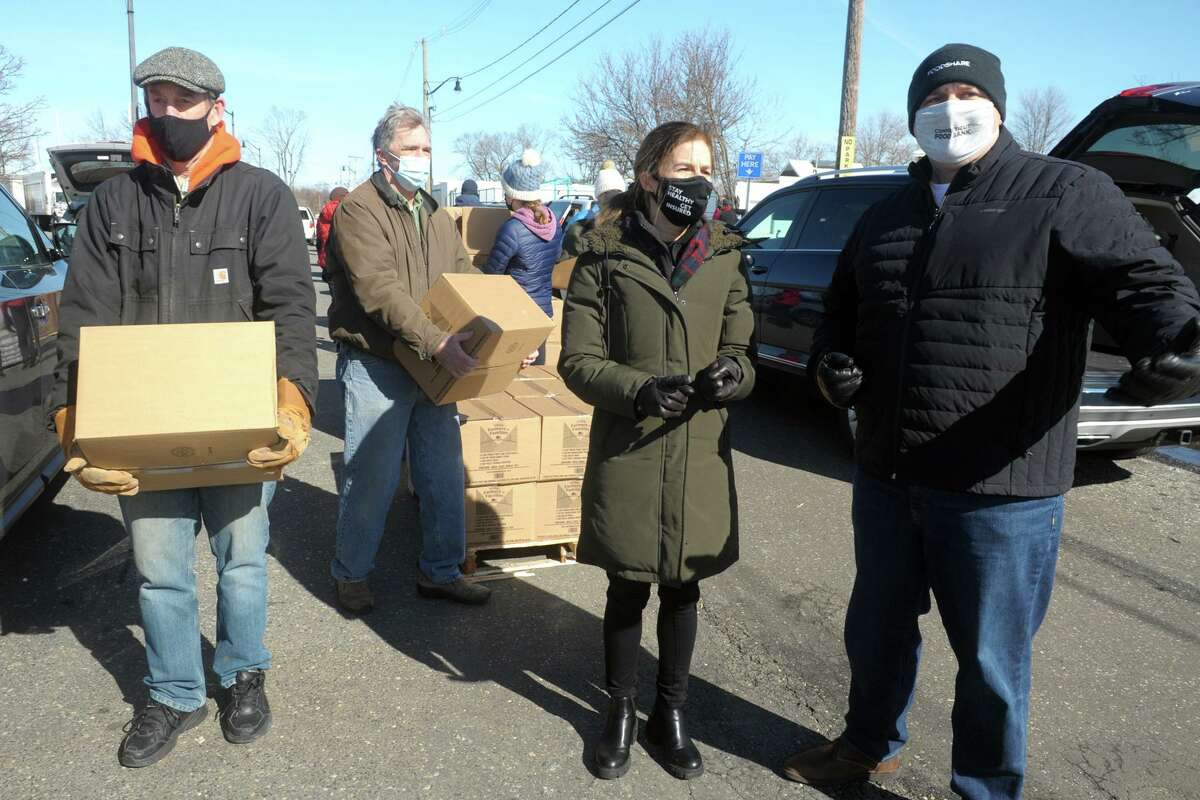 Lt. Gov. Susan Bysiewicz speaks with Jason Jakubowski, right, President and CEO of CT Food Bank/Foodshare during a visit to the weekly food distribution at Calf Pasture Beach, in Norwalk, Conn. Feb. 17, 2021.
