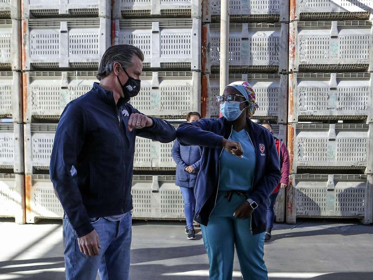 Gov. Gavin Newsom greets registered nurse Arlene Arrechea before holding a news conference in Coachella (Riverside County).