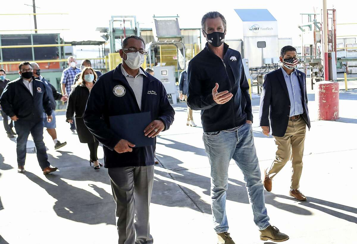 Gov. Gavin Newsom (right) walks with County Supervisor Manuel Perez before a news conference in Coachella (Riverside County). Newsom released details Wednesday on spending for small business grants, stimulus checks for individuals and housing for farmworkers infected by the coronavirus.