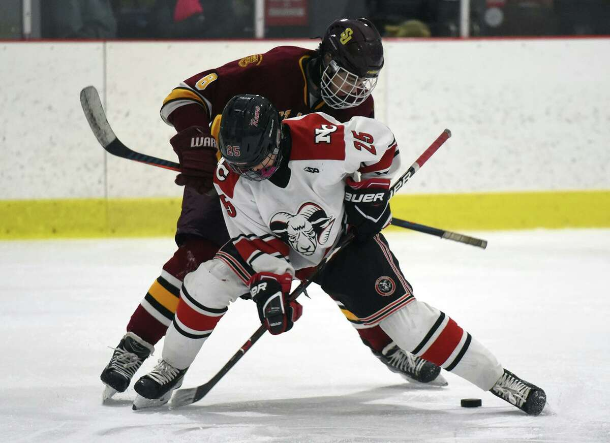 New Canaan's Carter Spain (25) and St. Joseph's Wyatt Chrisman (8) battle on a faceoff during a boys ice hockey game at the Darien Ice House on Monday, Jan. 7, 2019.