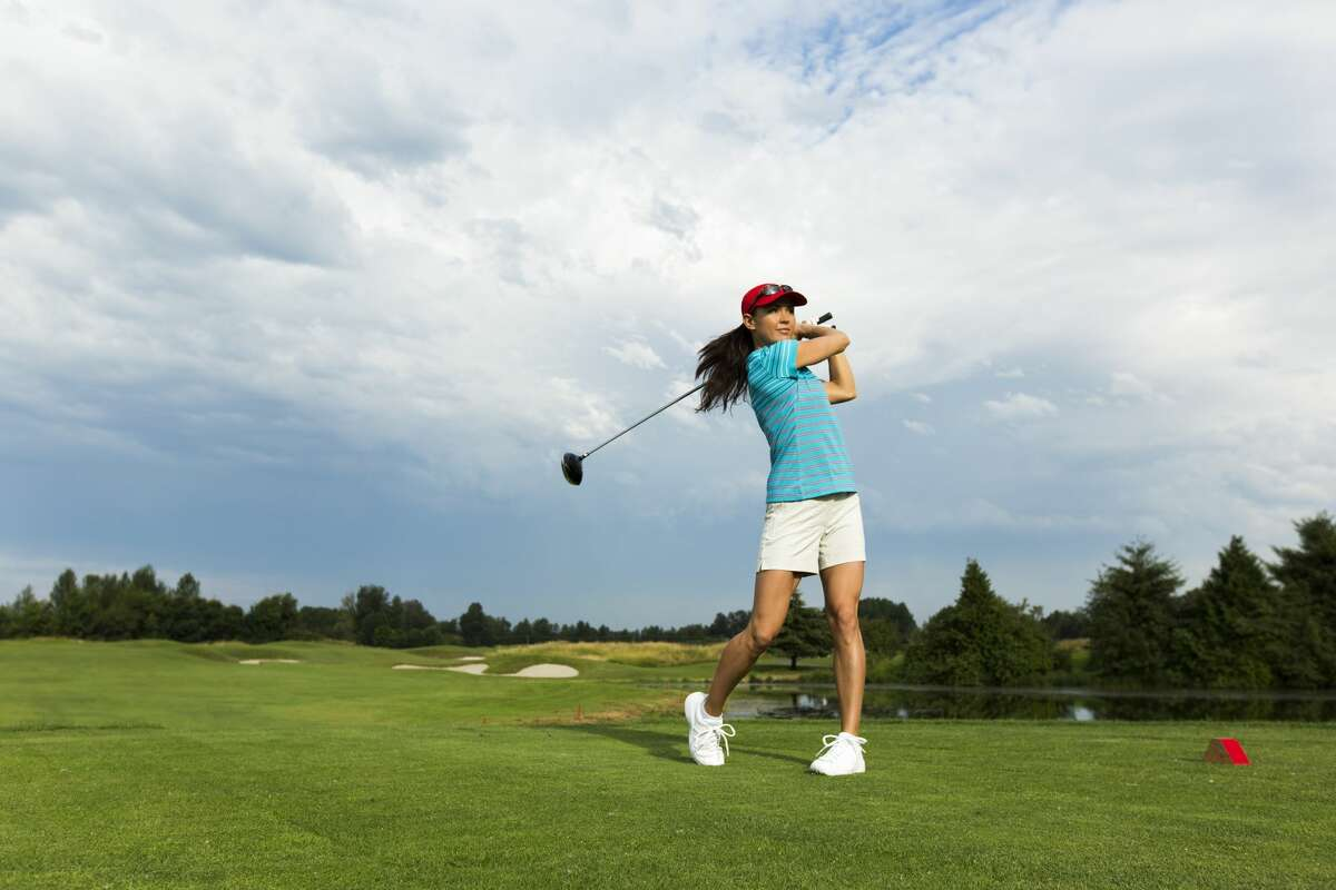 A woman driving a golf ball on a sunny summer day.
