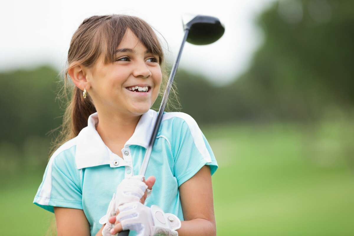 Happy little girl playing golf.