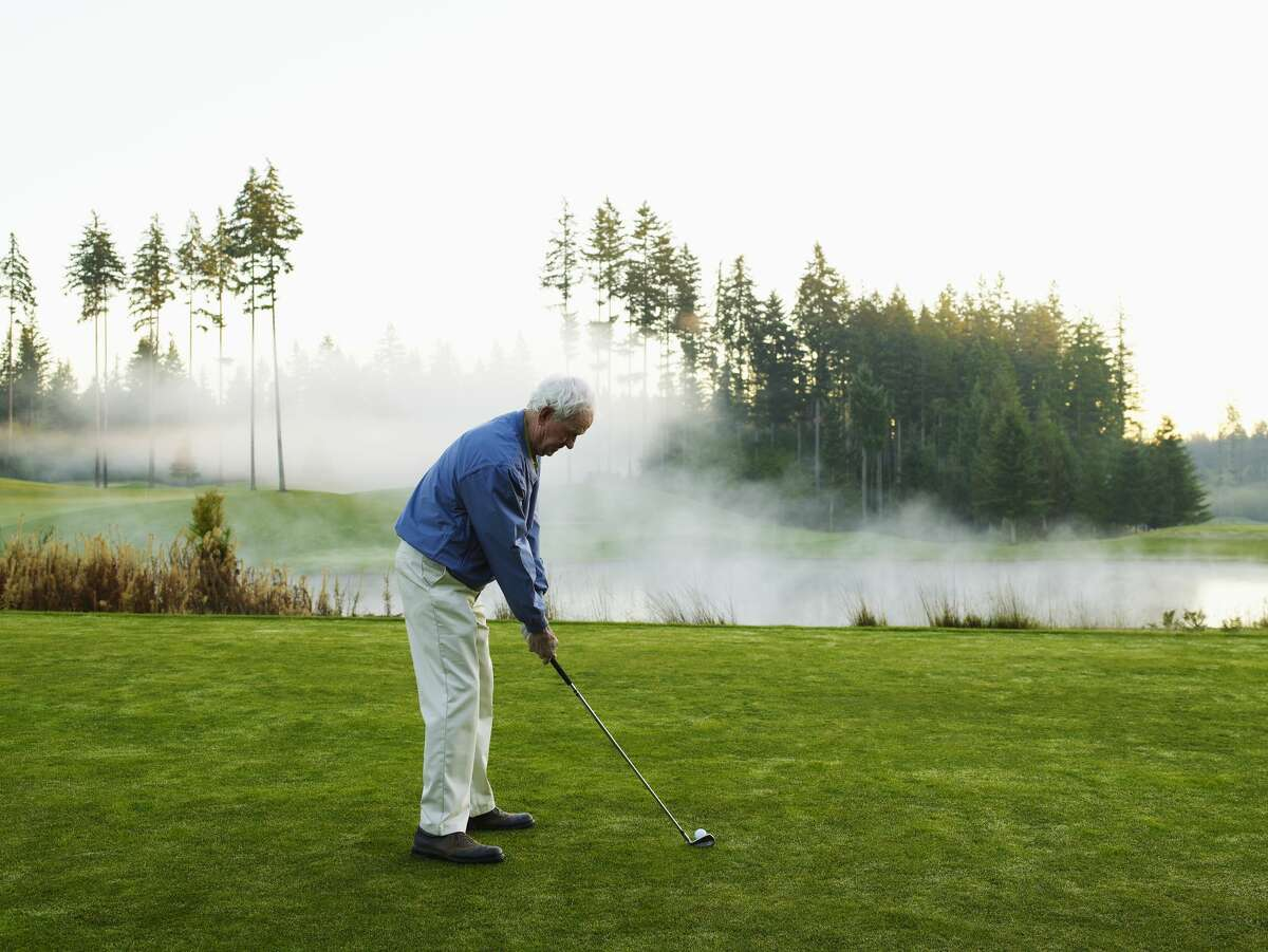 Man preparing to tee off on golf course.