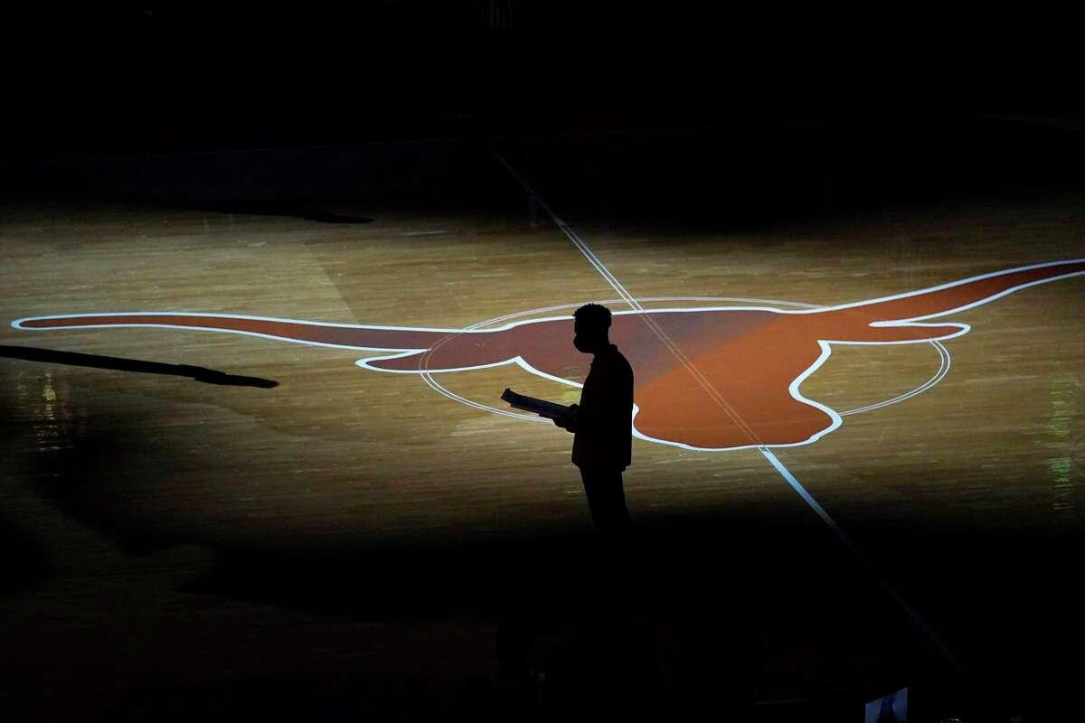 Texas head coach Shaka Smart is silhouetted against the team's logo before an NCAA college basketball game against TCU, Saturday, Feb. 13, 2021, in Austin, Texas. (AP Photo/Eric Gay)