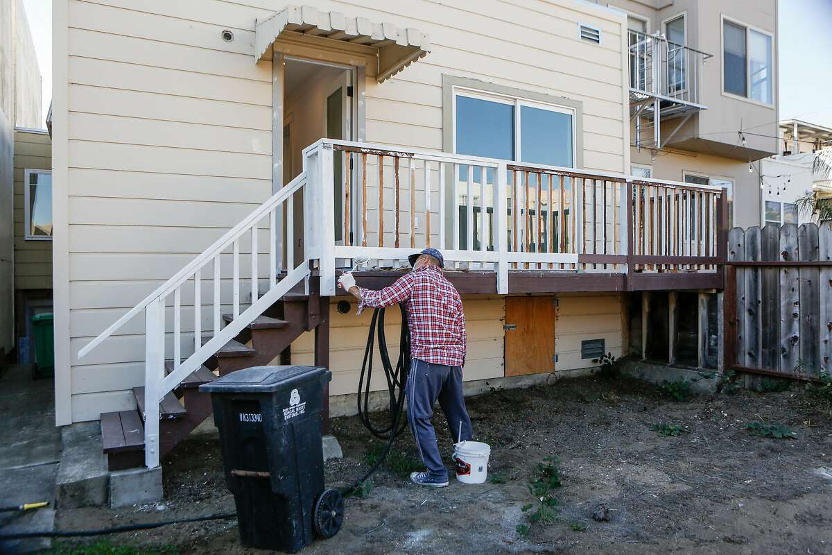 Phong Tang paints the outside banister of a single family home being renovated for sale in the Outer Sunset on Monday, October 26, 2020 in San Francisco, Calif.