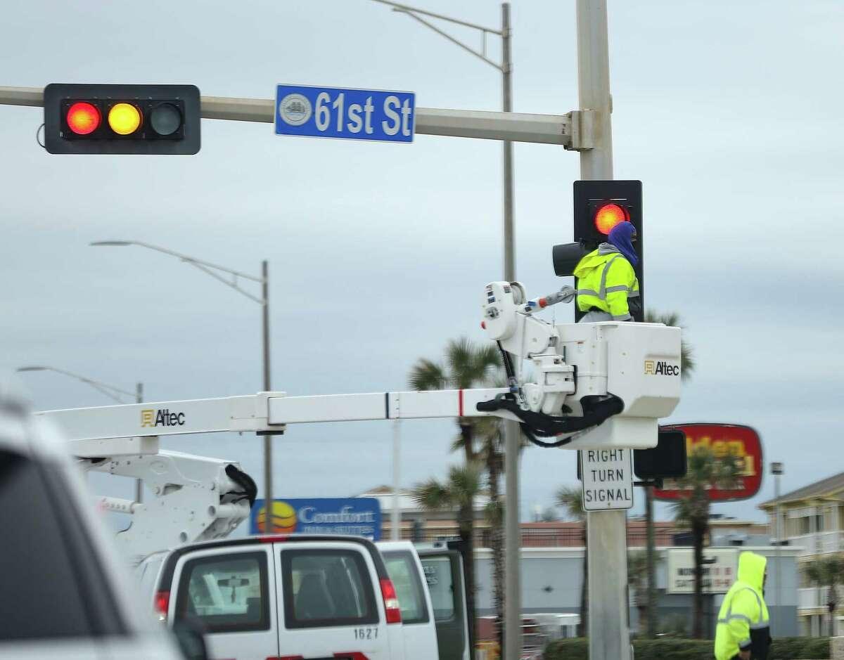 Utility crews work on malfunctioning lights on Seawall and 61st Street in Galveston on Wednesday, Feb. 17, 2021.