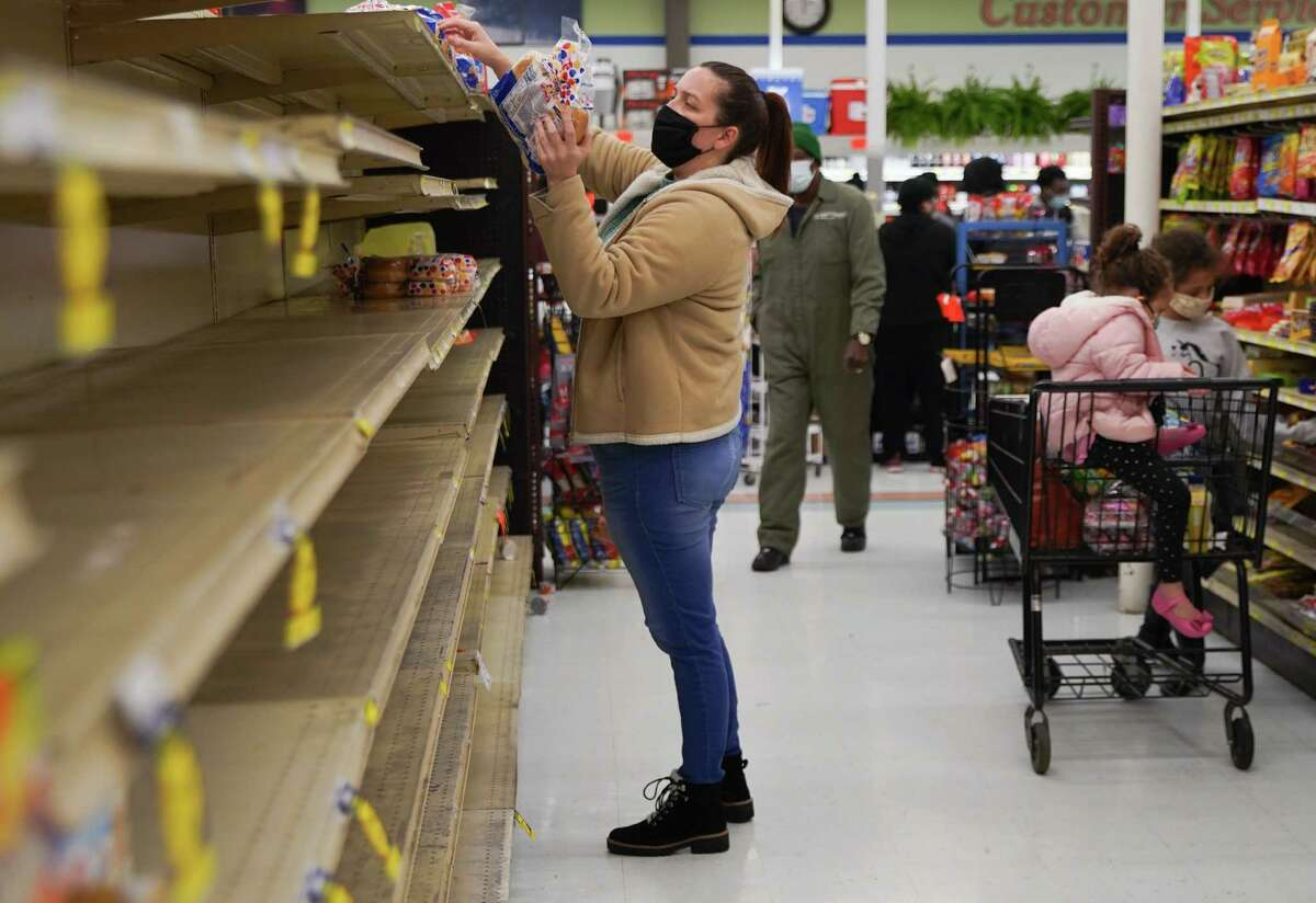 Markel Simpson grabs whats left of bread offerings for her family as she shops at Arnel's Market in Galveston on Wednesday, Feb. 17, 2021. Simpson, whose been out of power since 2am Monday, moved to a hotel room so they could have electricity and heat.