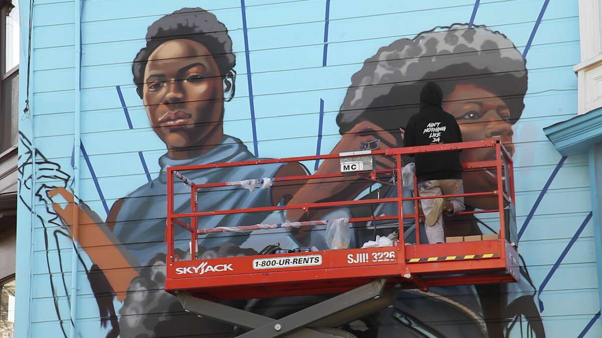 Artist Rachel Wolfe Goldsmith paints a mural featuring the women of the Black Panther Party.