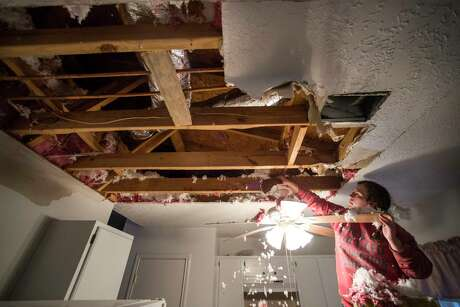 Hannah Siqueiros, clears insulation from a damaged ceiling after a broken pipe was repaired pipe above the kitchen in Michelle Toy's home Wednesday, Feb. 17, 2021 in Spring. Water from a damaged pipe above the kitchen caused the ceiling to collapse.