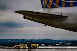 Heavy equipment removes snow from the runways and taxiways at San Antonio International Airport on Wednesday, Feb. 17, 2021. The airport has been closed since Monday due to snow and extreme cold weather.