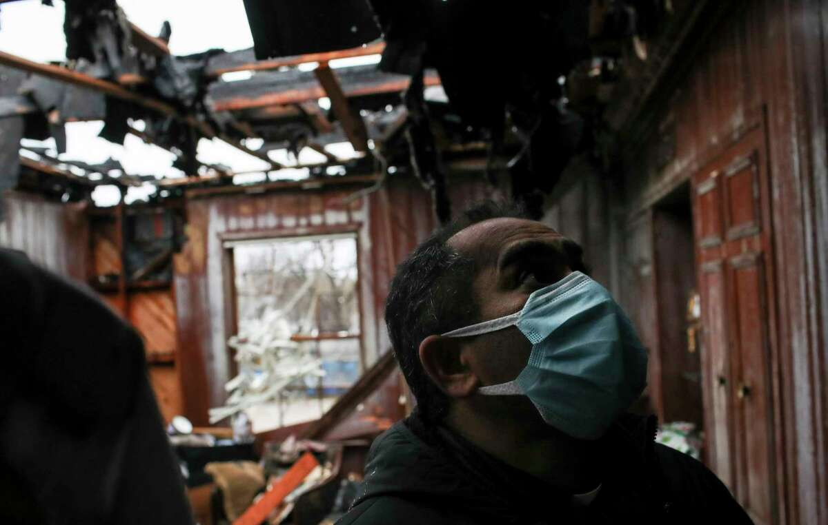Father Anil Thomas looks around a building damaged in a fire the previous day Wednesday, Feb. 17, 2021, at Holy Name Catholic Church in Houston.