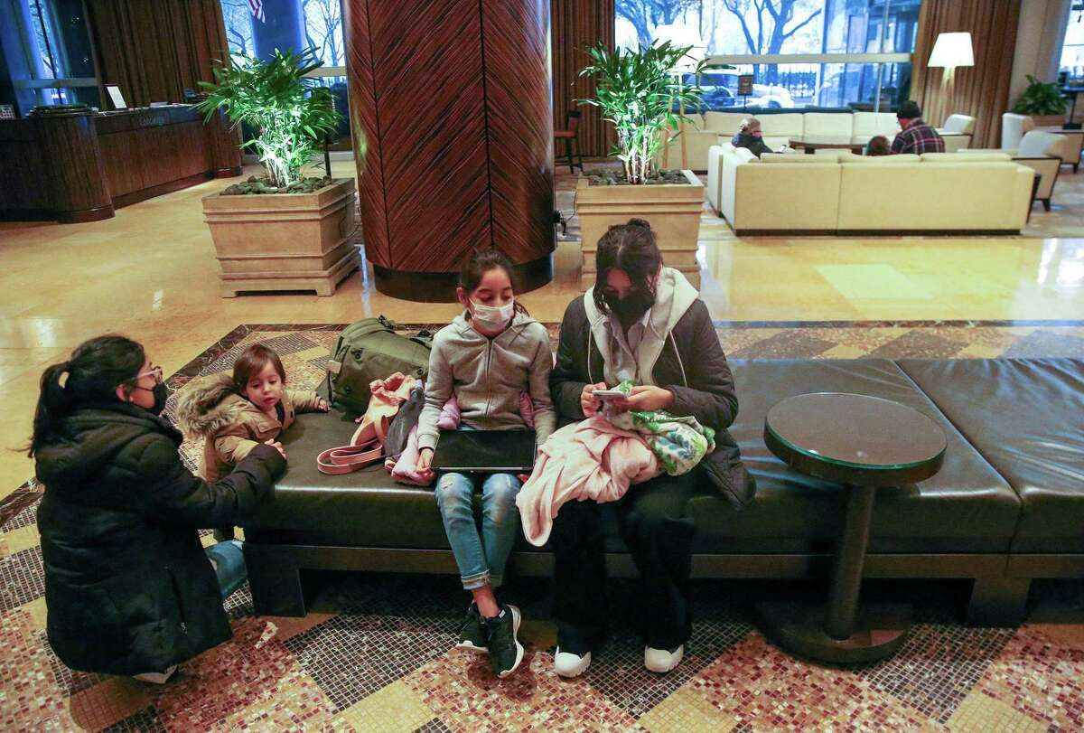 The Morales family waits in the lobby of the Hilton America Hotel in Houston, Texas on February 17, 2021. - The Morales family had to vacate their hotel February 14, 2021 when they lost power and the pipes burst inside their home.