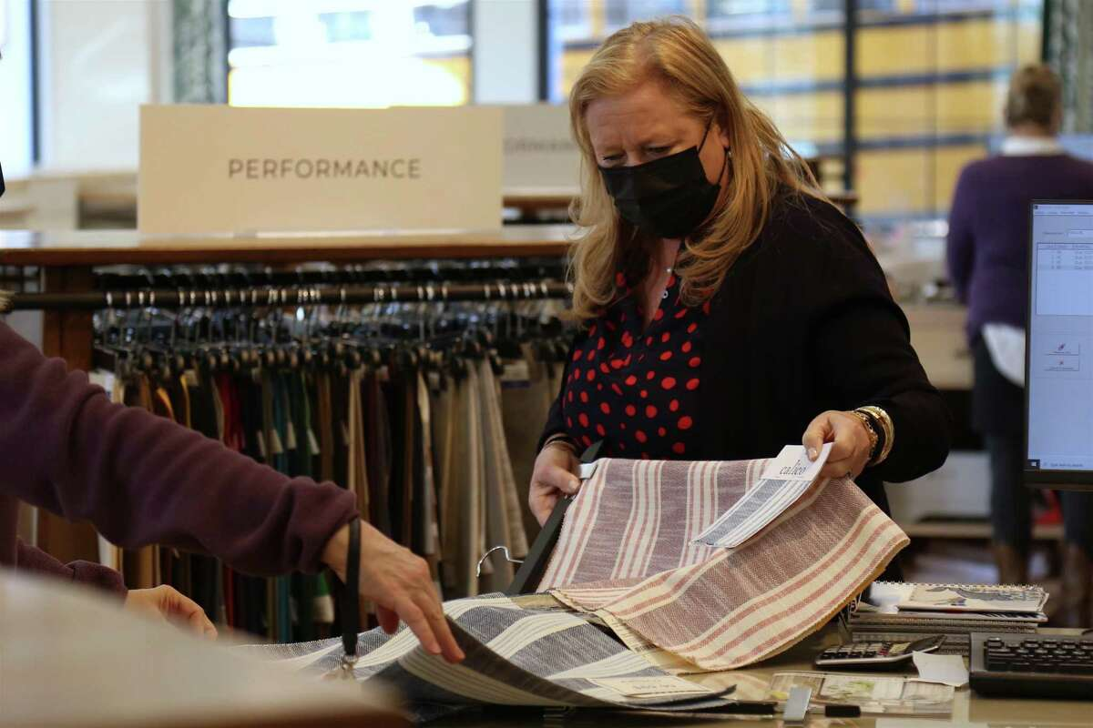 Designer Shaun Amberg discusses fabric with a customer at Calico on Tuesday, Feb. 16, 2021, in Westport, Conn.