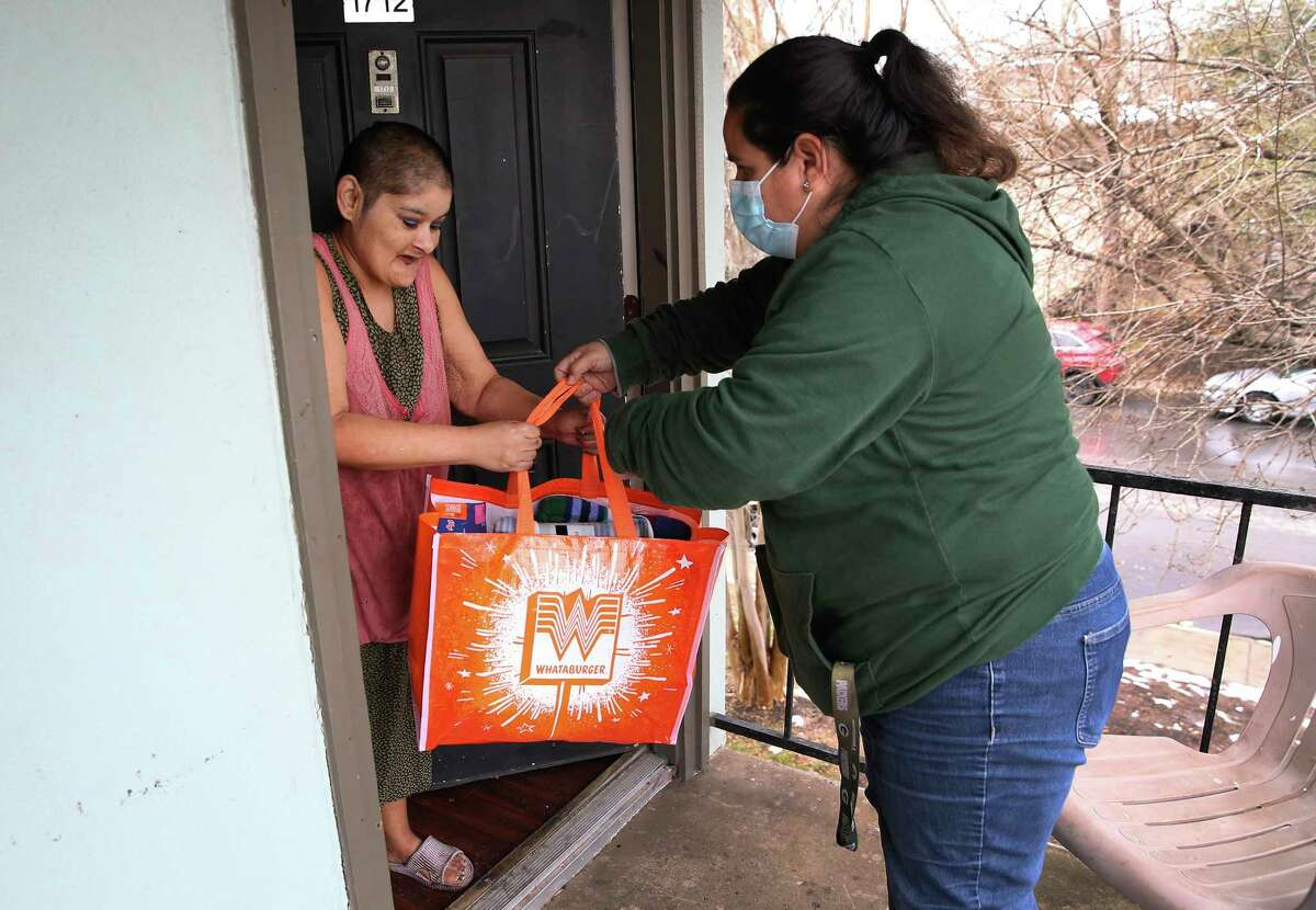 Maricela Avila of Eagles Flight hands a care package to cancer patient Martha Cordero.