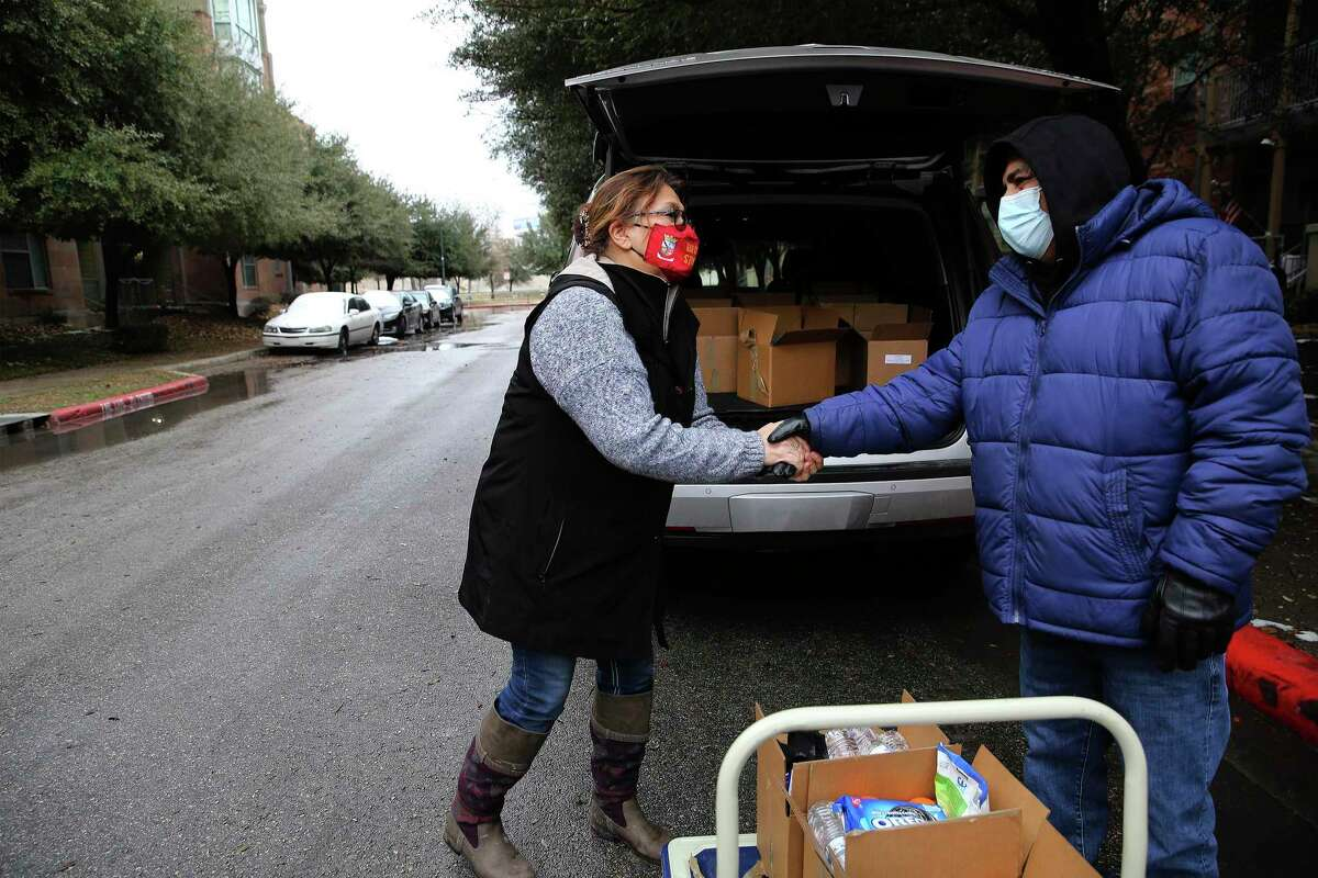 Pam Allen (left) of Eagles Flight receives a handshake in gratitude from Larry Uresti who requested assistance for food and other items on Wednesday, Feb 17, 2021. Eagles Flight is among the nonprofits providing for those in need during the winter storm. On Wednesday, Allen and her staff were busily packing boxes and care packages with food, personal hygiene and other assorted items for people in need during the winter weather crisis. They then took the packages directly to the families who requested assistance. In total about 180 care packages were distributed by Eagles Flight on Wednesday to the elderly and families needing supplies as power outages continue to ravage the area. The non-profit services about 300 families per week.