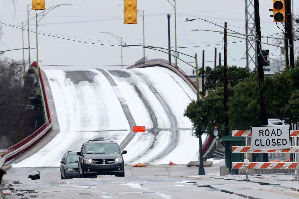 Traffic moves along Guadalupe Street as the bridge over the railroad tracks remains closed due to icing, Wednesday, Feb. 17, 2021. Overpasses throughout the area remained closed to traffic due to icing. This week's blast of arctic weather paralyzed much of San Antonio and did what even the pandemic frequently couldn't do: It forced residents to stay home.