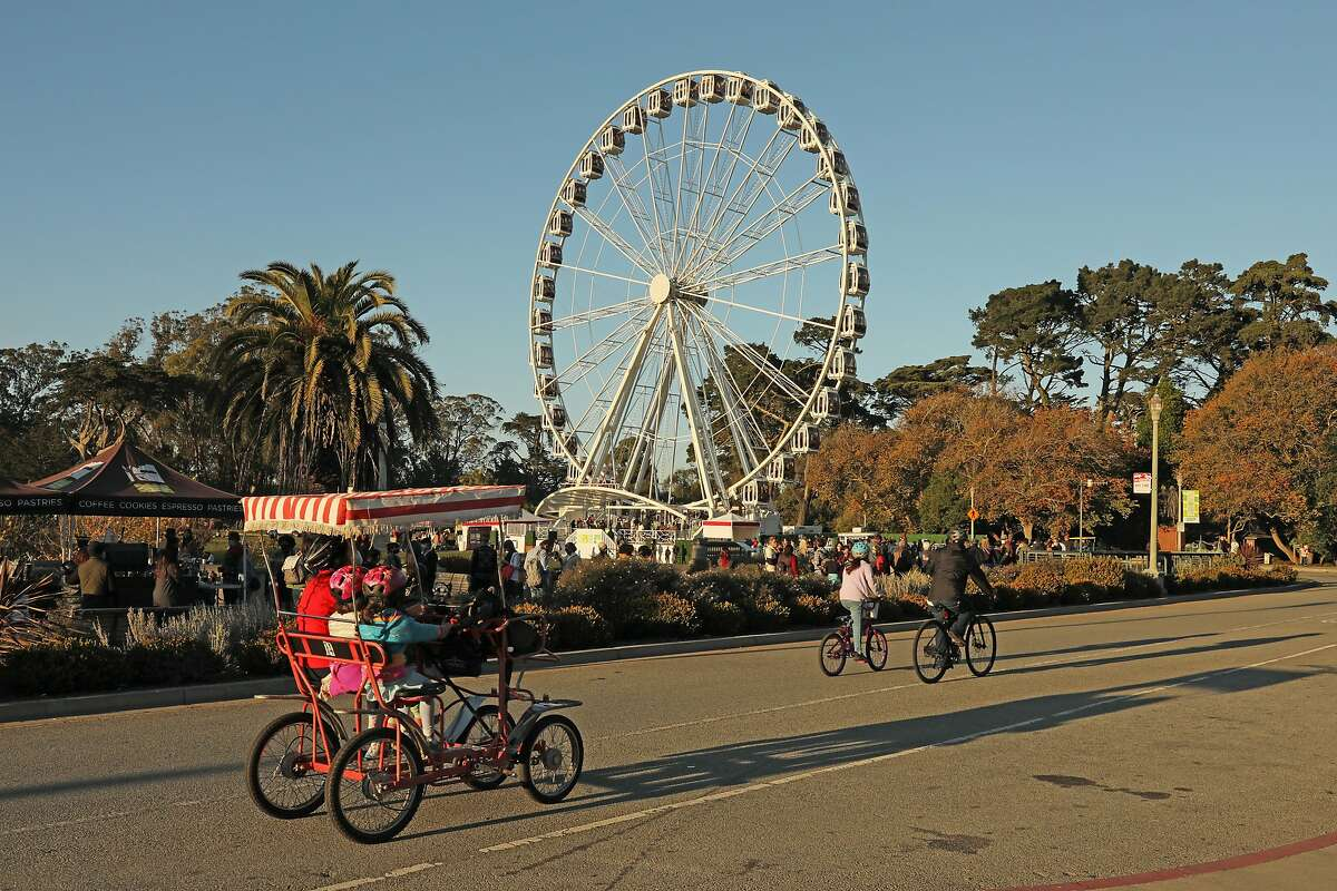 Bikers pass a long line of people for the SkyStar Observation Wheel Golden Gate Park, Saturday, Nov. 28, 2020, in San Francisco, Calif.