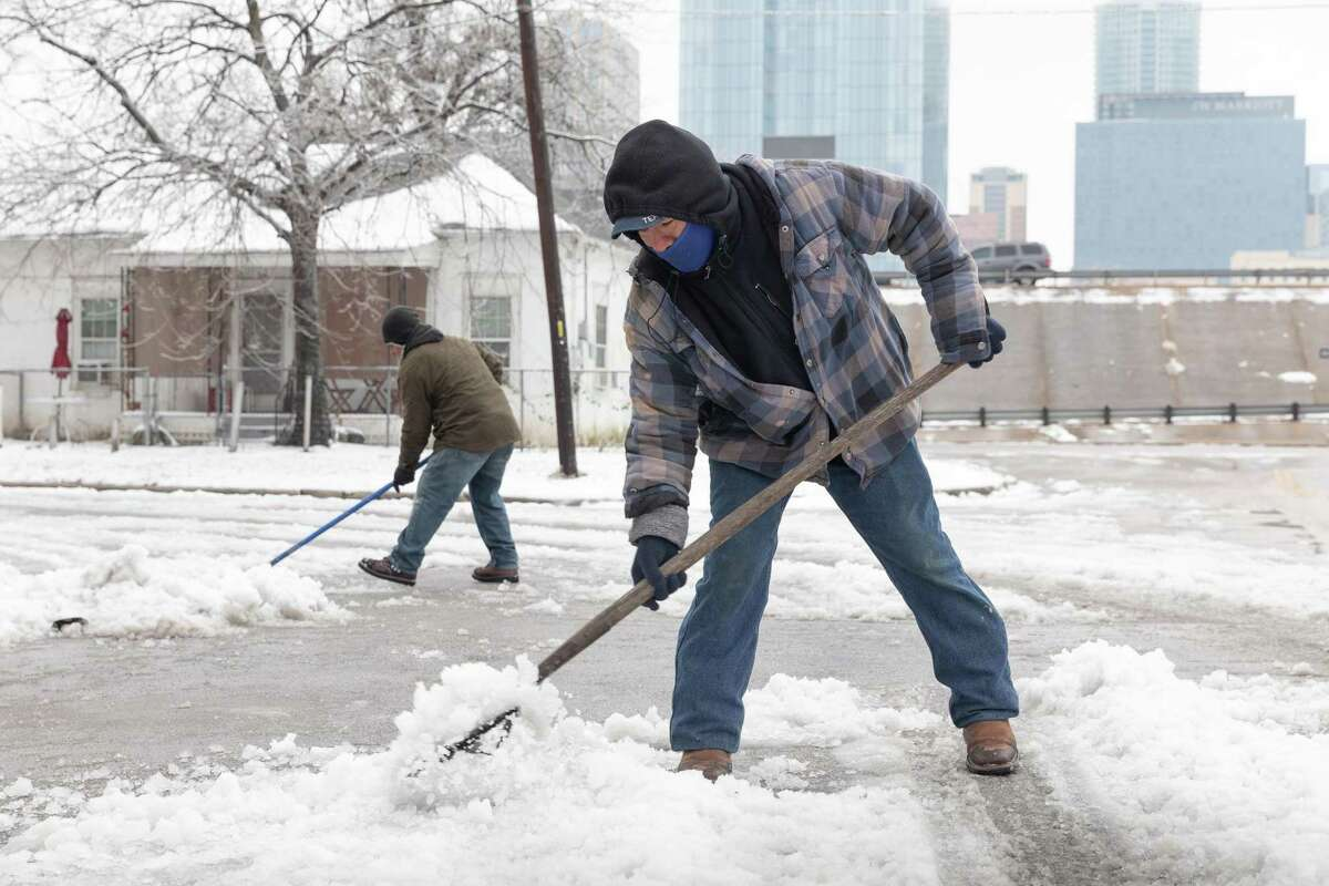 Residents shovel snow from the street in front of a home in East Austin, Texas, U.S., on Wednesday, Feb. 17, 2021. The crisis that has knocked out power for days to millions of homes and businesses in Texas and across the central U.S. is getting worse, with blackouts expected to last until at least Thursday. Photographer: Thomas Ryan Allison/Bloomberg