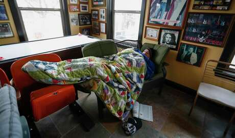 Heights resident Todd Green huddles beneath multiple blankets as he tries to stay warm in his home without power and running water, in Houston, Wednesday, February 17, 2021, after a winter storm left people without power and water along with freezing temperatures.