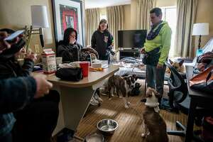 Apryl Minor, April Hobby and Autumn Riley listen to instructions Wednesday from an Austin Mutual Aid volunteer. The group moved to a shelter after their hotel lost power.