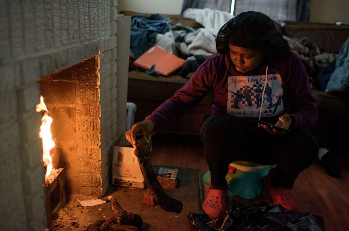 Linda McCoy throws wood onto a fire to heat in her home in Houston on Wednesday. Public safety officials warned about the dangers of carbon monoxide poisoning after emergency calls related to people using charcoal grills to try to heat their homes.
