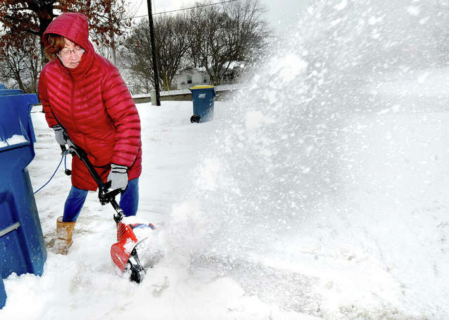 Judy Budzileni of Edwardsville clears snow from her driveway at her home on Gerber Road Wednesday. She said that she needed to do so before leaving for work. Photo: Thomas J. Turney | The Intelligencer
