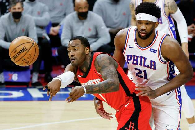 The Houston Rockets' John Wall (1) passes ahead of pressure from the Philadelphia 76ers' Joel Embiid (21) during the first quarter against at Wells Fargo Center in Philadelphia on Wednesday, Feb. 17, 2021. Despite 28 points from Wall, the Sixers posted a 118-113 as Embiid missed a triple-double by one assist. Photo: Tim Nwachukwu, TNS / 2021 Getty Images 2021 Getty Images