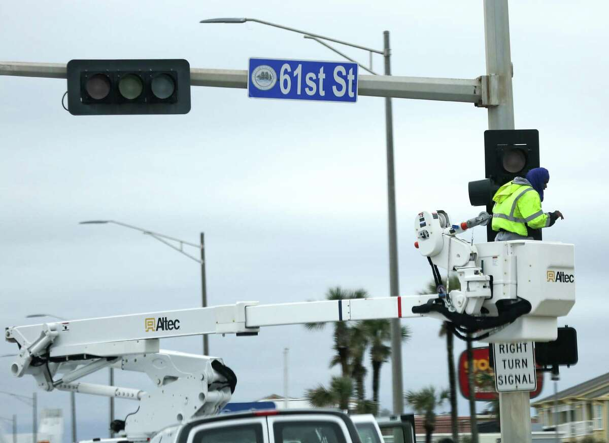 Utility crews work on malfunctioning lights on Seawall and 61st Street in Galveston on Wednesday.