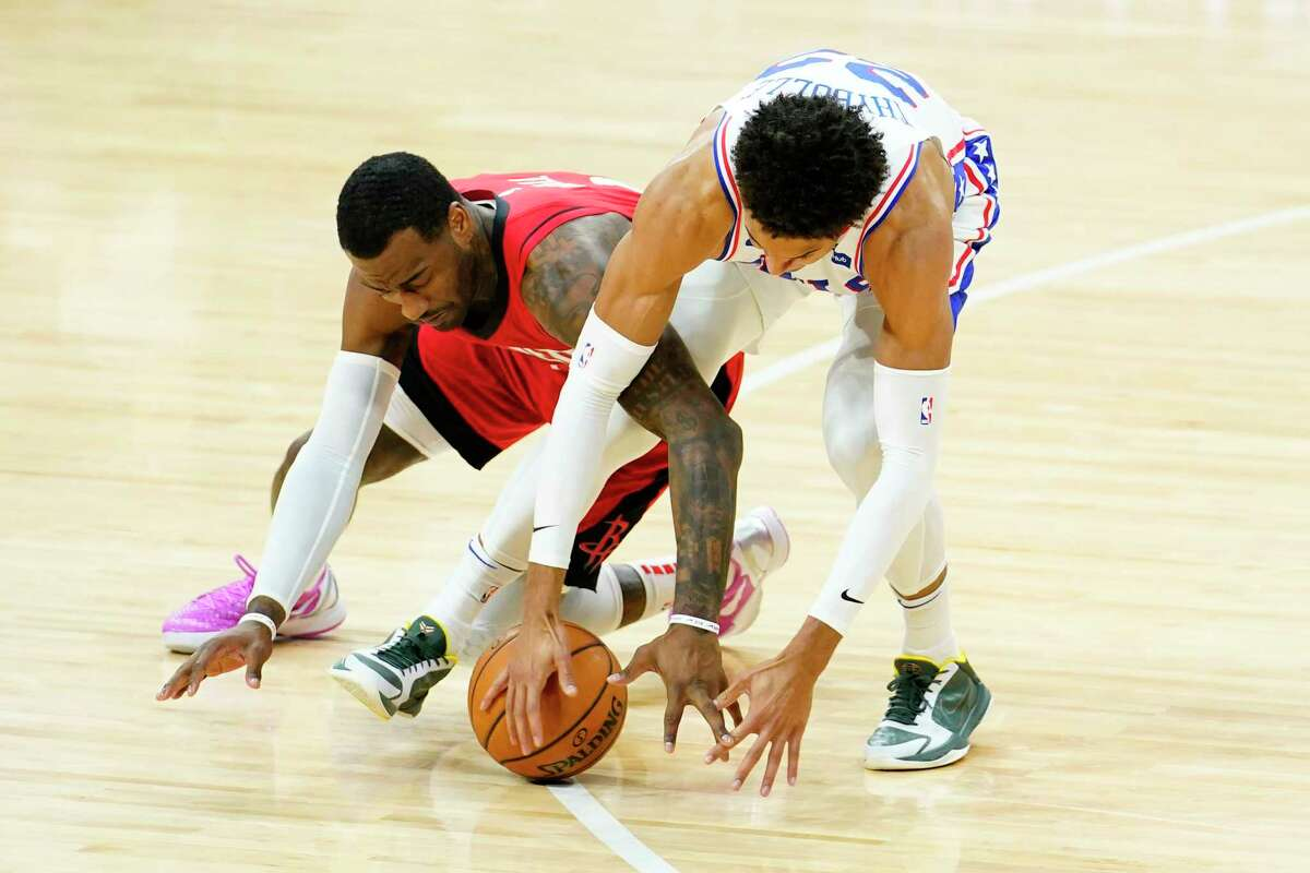 Houston Rockets' John Wall, left, and Philadelphia 76ers' Matisse Thybulle reach for a loose ball during the second half of an NBA basketball game, Wednesday, Feb. 17, 2021, in Philadelphia. (AP Photo/Matt Slocum)