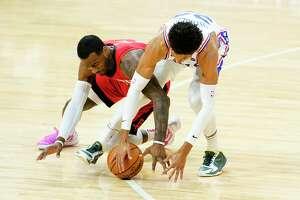 Houston Rockets' John Wall, left, and Philadelphia 76ers' Matisse Thybulle reach for a loose ball during the second half of an NBA basketball game, Wednesday, Feb. 17, 2021, in Philadelphia. (AP Photo/Matt Slocum)